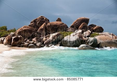Rocky outcrop on a sandy beach with a calm blue sea and golden sand symbolic of a summer vacation in the tropics