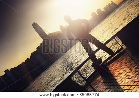 Silhouette of a man standing with his arms on his hips on a promenade overlooking Hong Kong city at sunrise or sunset in the flare from the sun, tilted angle conceptual image