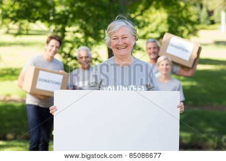 Happy volunteer grandmother holding blank on a sunny day