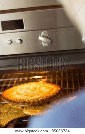 Woman taking fresh pie out of oven at home in the kitchen