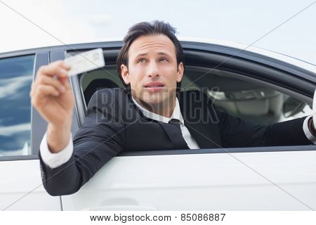 Businessman showing his driver license in his car