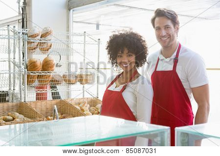 Portrait of happy co-workers standing behind the counter at the bakery