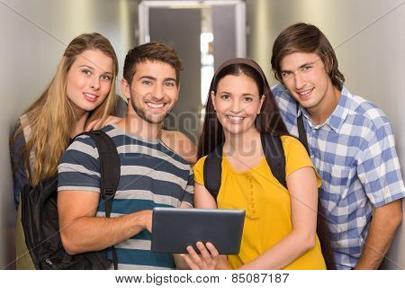 Portrait of happy students using digital tablet at college corridor