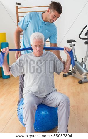 Senior man training with his coach in fitness studio
