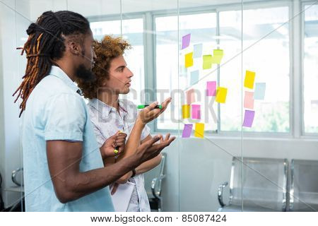 Creative business team looking at adhesive notes in office