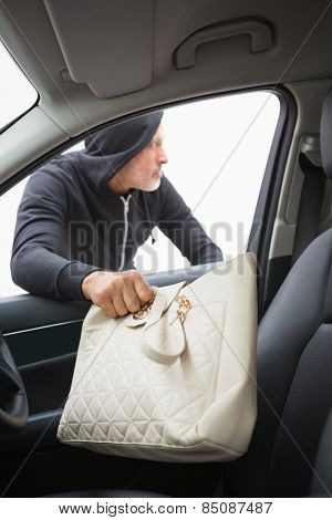 Thief breaking into car and stealing hand bag in broad daylight