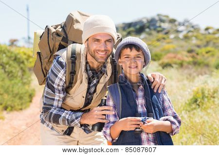 Father and son hiking in the mountains on a sunny day