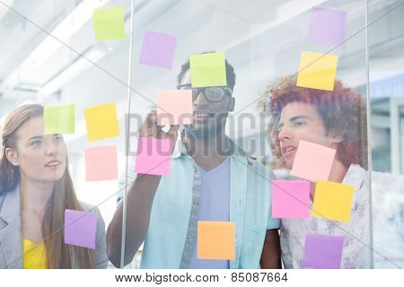 Creative business team writing on adhesive notes in office
