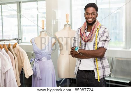 Portrait of confident male fashion designer standing with arms crossed