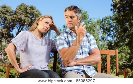 Couple having an argument on park bench on a sunny day