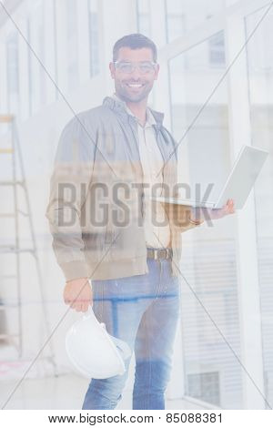 Portrait of confident male architect with hardhat and laptop in office