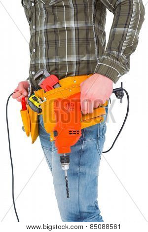 Smiling manual worker holding drill machine on white background