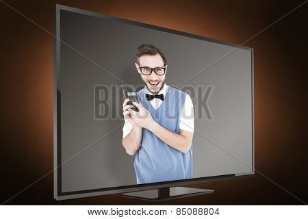 Geeky hipster holding a retro cellphone against orange background with vignette