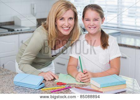 Happy mother helping daughter doing homework