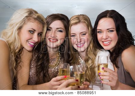 Friends drinking champagne against bleached wooden planks background