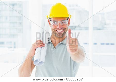 Portrait of happy handyman with rolled up blueprint gesturing thumbs up in office