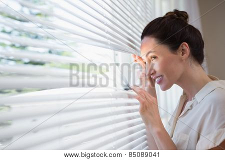Woman peeking through the blinds from inside