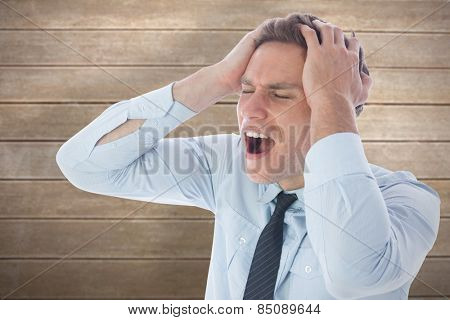 Stressed businessman with hands on head against wooden surface with planks