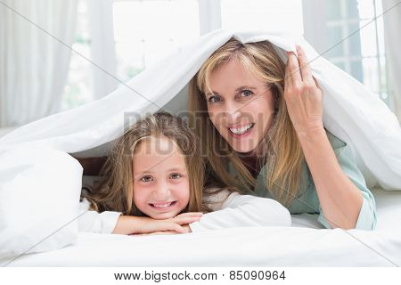 Mother and daughter looking at camera under the duvet at home in the bedroom