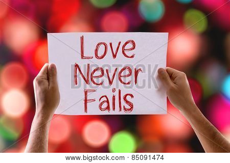 Love Never Fails card with colorful background with defocused lights