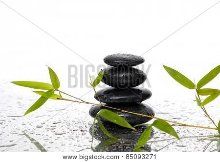 Stacked black stones and green bamboo leaf on wet background