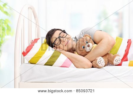 Childish young man sleeping with a teddy bear at home
