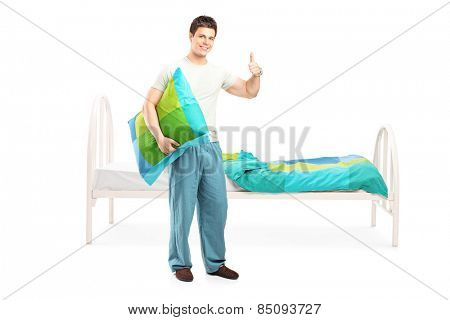 Full length portrait of a man in pajamas giving thumb up and standing by his bed isolated on white background