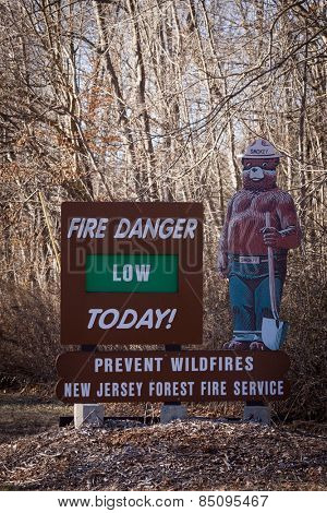 ANDOVER, NEW JERSEY - DECEMBER 2014: A wooden sign to help prevent forest fires with Smokey The Bear indicating fire danger is low displayed on Rt 206 by the NJ Forest Fire Service.