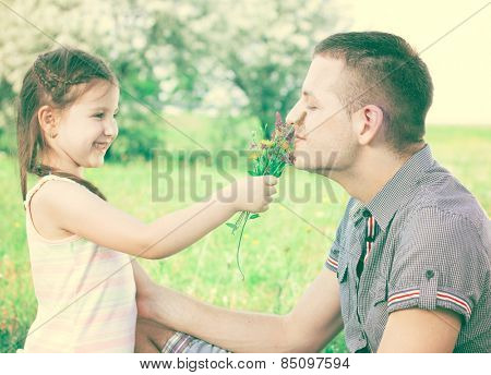 Little girl with flowers in hand and uncle smiling and enjoy in beautiful day