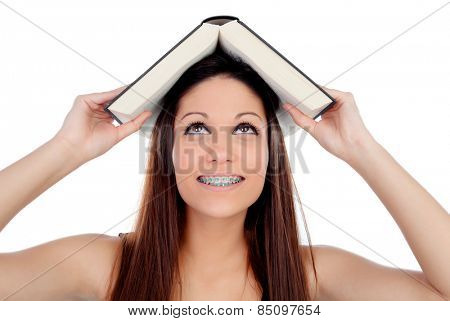 Attractive student woman with brackets an a book on the head isolated on a white background