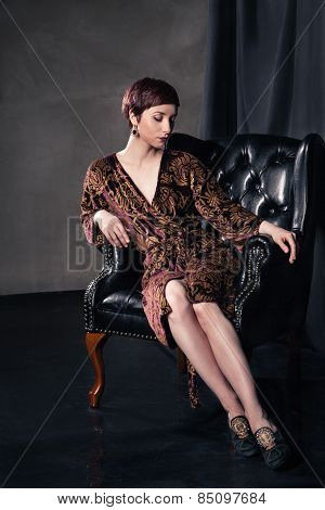 Beautiful woman wearing short dress sitting in  armchair