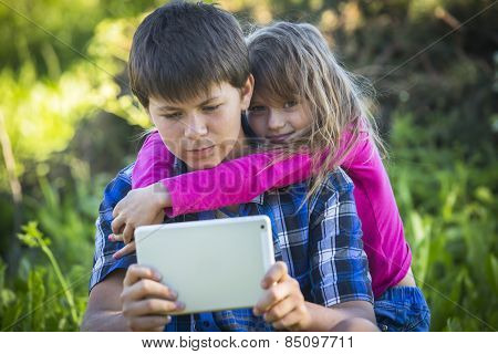 Teenager with his younger sister sitting outdoors and using the tablet.
