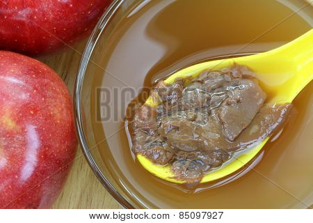 A spoon of Mother enzymes on a bowl of raw and unfiltered organic apple cider vinegar
