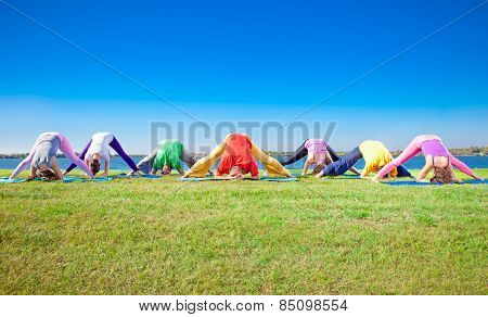 Young people practice Yoga asana on lakeside. Yoga concept.