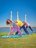 picture of suny  - Tree people practice Yoga asana at lakeside on suny day - JPG