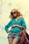 stock photo of blouse  - Gorgeous young woman with beautiful wavy hair wearing casual blouse and jeans shorts posing outdoor - JPG