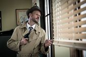 foto of peek  - Attractive spy agent peeking from an office window film noir - JPG