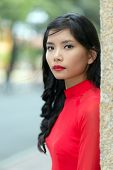 stock photo of turn-up  - Attractive serious young Vietnamese woman in a vivid red dress leaning on a wall in an urban street turning to look at the camera - JPG