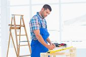 stock photo of workbench  - Handyman working at workbench in bright office - JPG