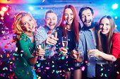 stock photo of flute  - Young people with champagne flutes in confetti - JPG