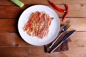 image of bacon strips  - Strips of bacon in white plate with spices - JPG