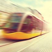 stock photo of tram  - Modern tram in motion blur and sunlight - JPG