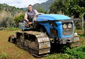 stock photo of grass-cutter  - Tractor driver smiling cutter vegetable garden with a crawler tractor - JPG