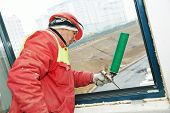 stock photo of insulator  - construction builder works with polyurethane foam during frame insulation at window installation - JPG