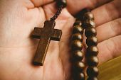 image of rosary  - Hand holding wooden rosary beads overhead shot - JPG