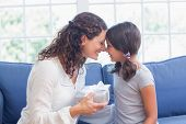 pic of cute  - Cute girl offering gift to her mother in the living room - JPG