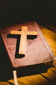 stock photo of crucifix  - Crucifix icon resting on the bible on wooden table - JPG