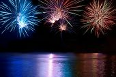 stock photo of firework display  - Blue red and white colorful fireworks above the river - JPG