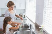 image of daughter  - Mother and daughter washing up at home in kitchen - JPG