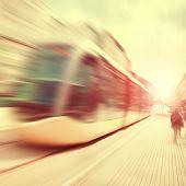 foto of tram  - Modern tram in motion blur on the street at sunset - JPG